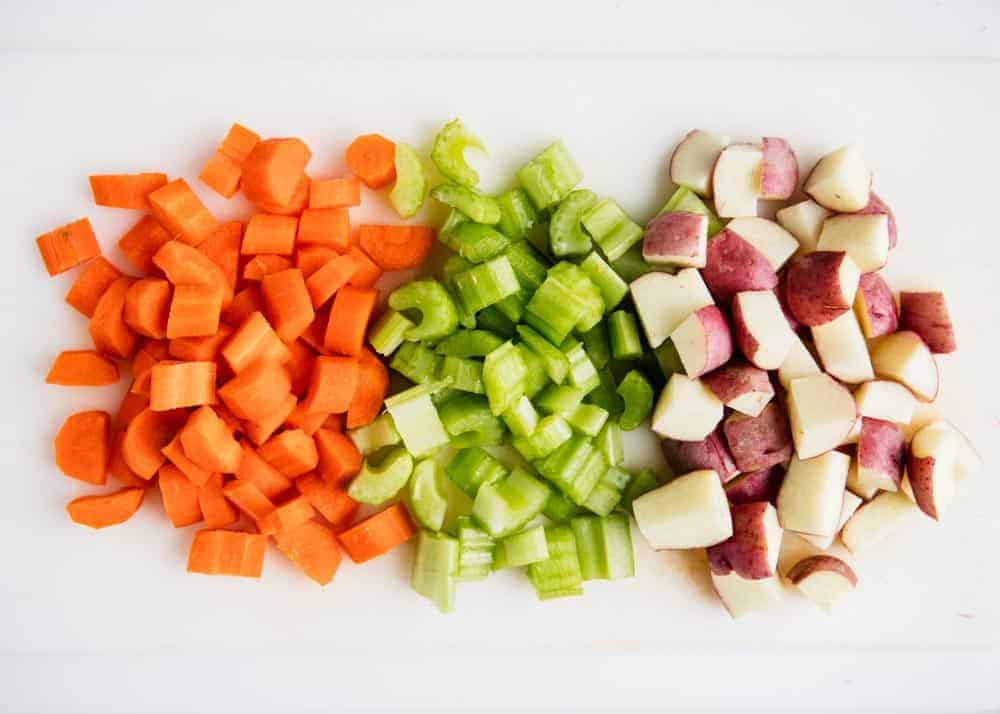 cutting board with sliced carrots, celery and potatoes