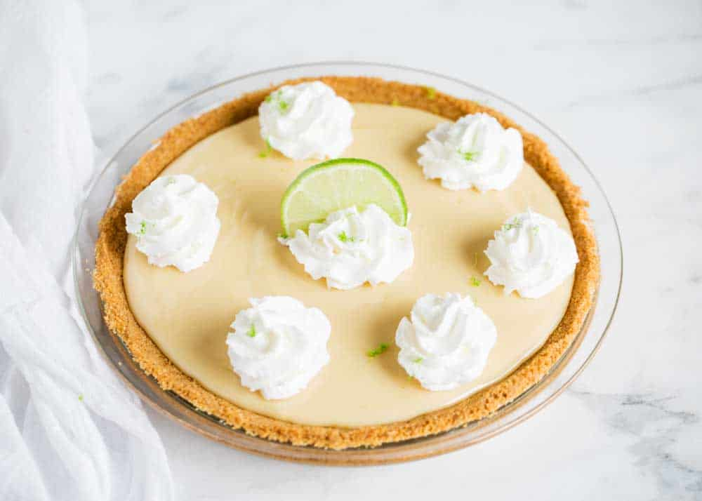 key lime pie topped with dollops of whipped cream and a lime slice