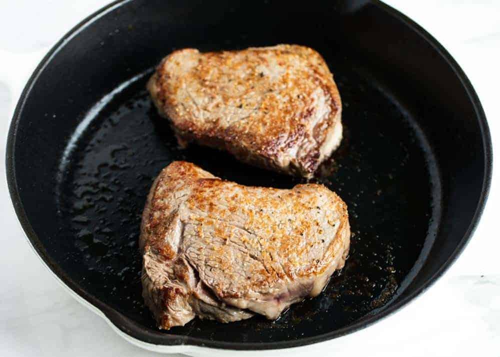 2 steaks in a black skillet