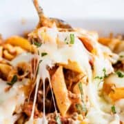 A close up of cheesy baked ziti on a fork