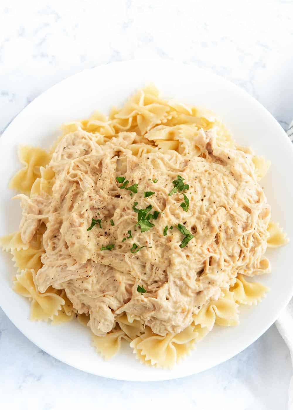 creamy Italian chicken served over noodles on a white plate