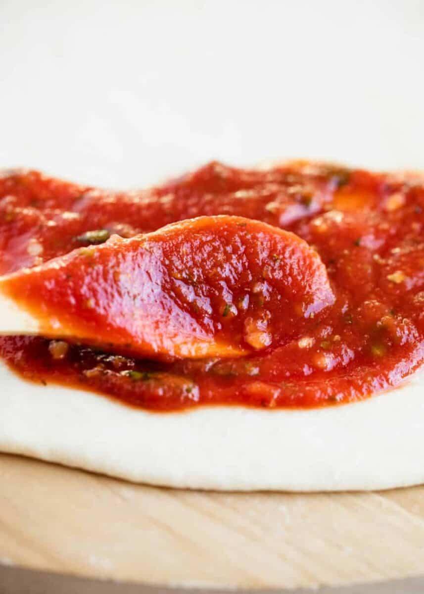 pizza sauce spread on pizza dough