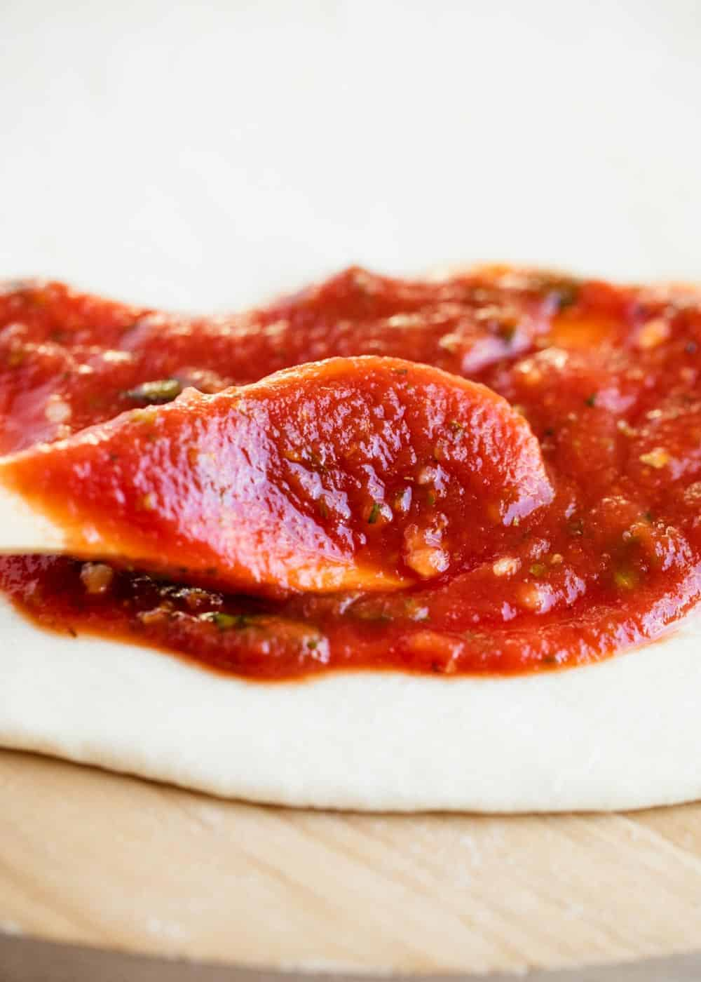 pizza sauce spread on pizza dough