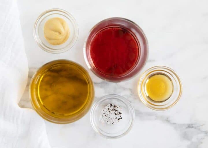 ingredients for vinaigrette in bowls on counter