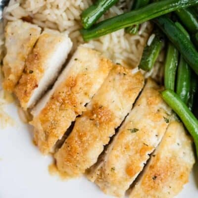parmesan crusted chicken sliced on a plate with green beans and rice