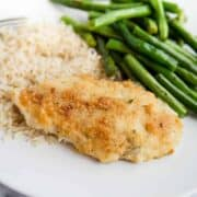 A plate of parmesan crusted chicken, green beans and rice