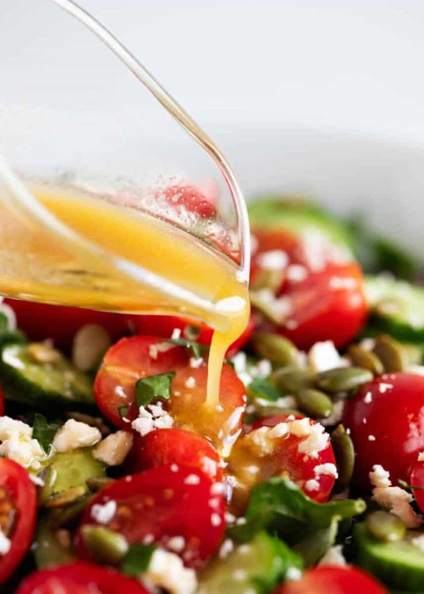 pouring vinaigrette over chopped salad