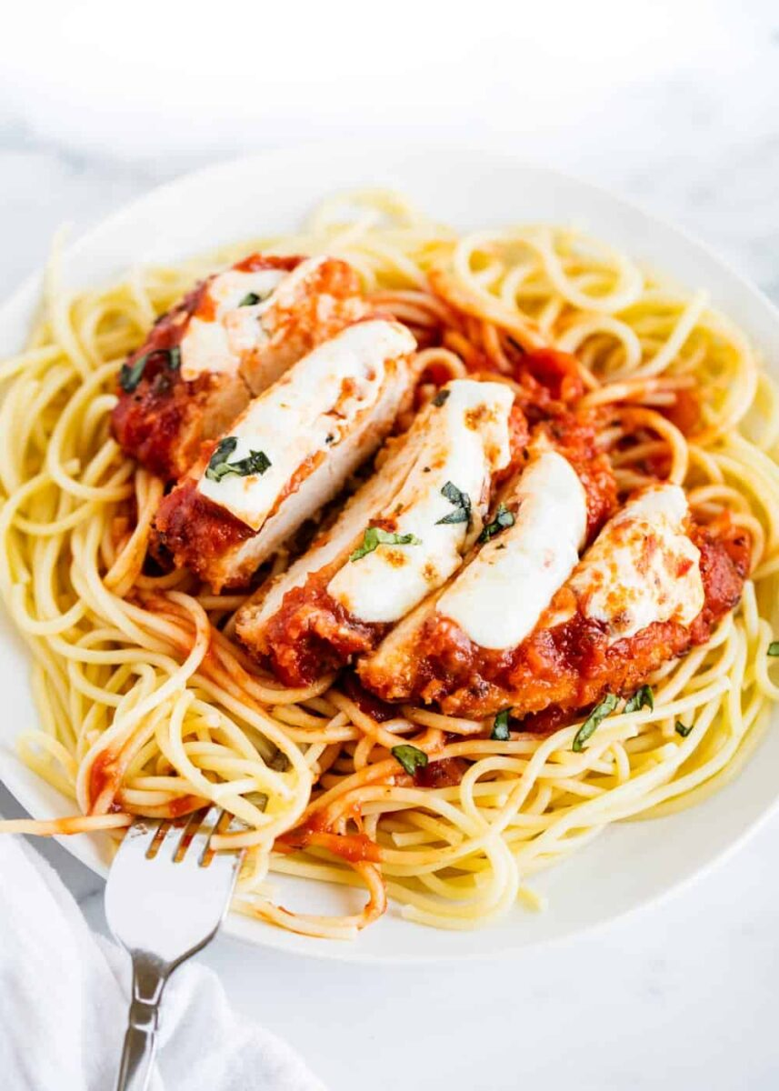 sliced chicken parmesan served over noodles on white plate
