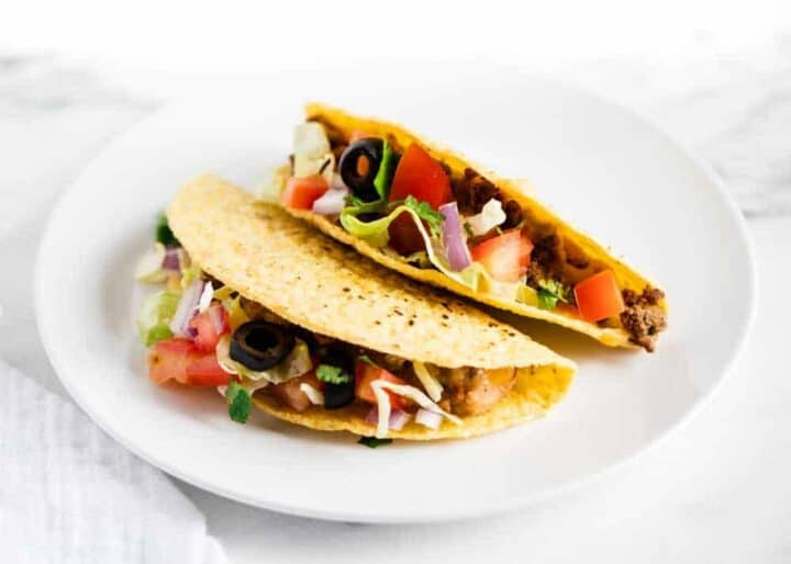 two ground beef tacos on white plate