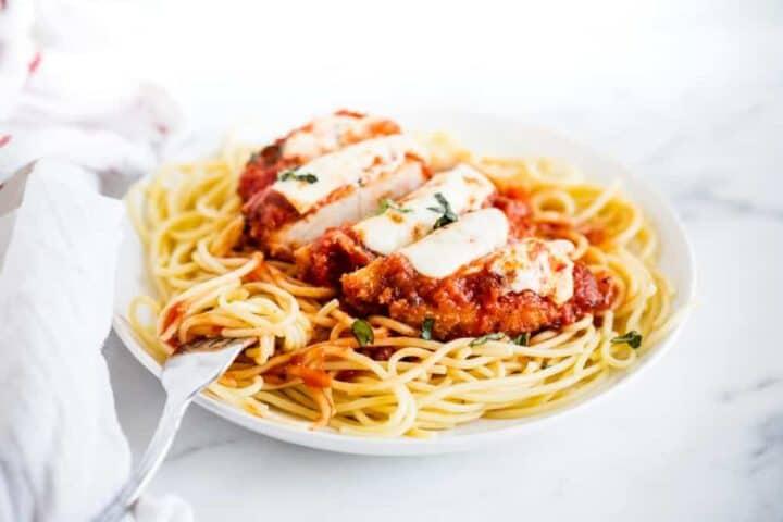 sliced chicken parmesan served over spaghetti noodles
