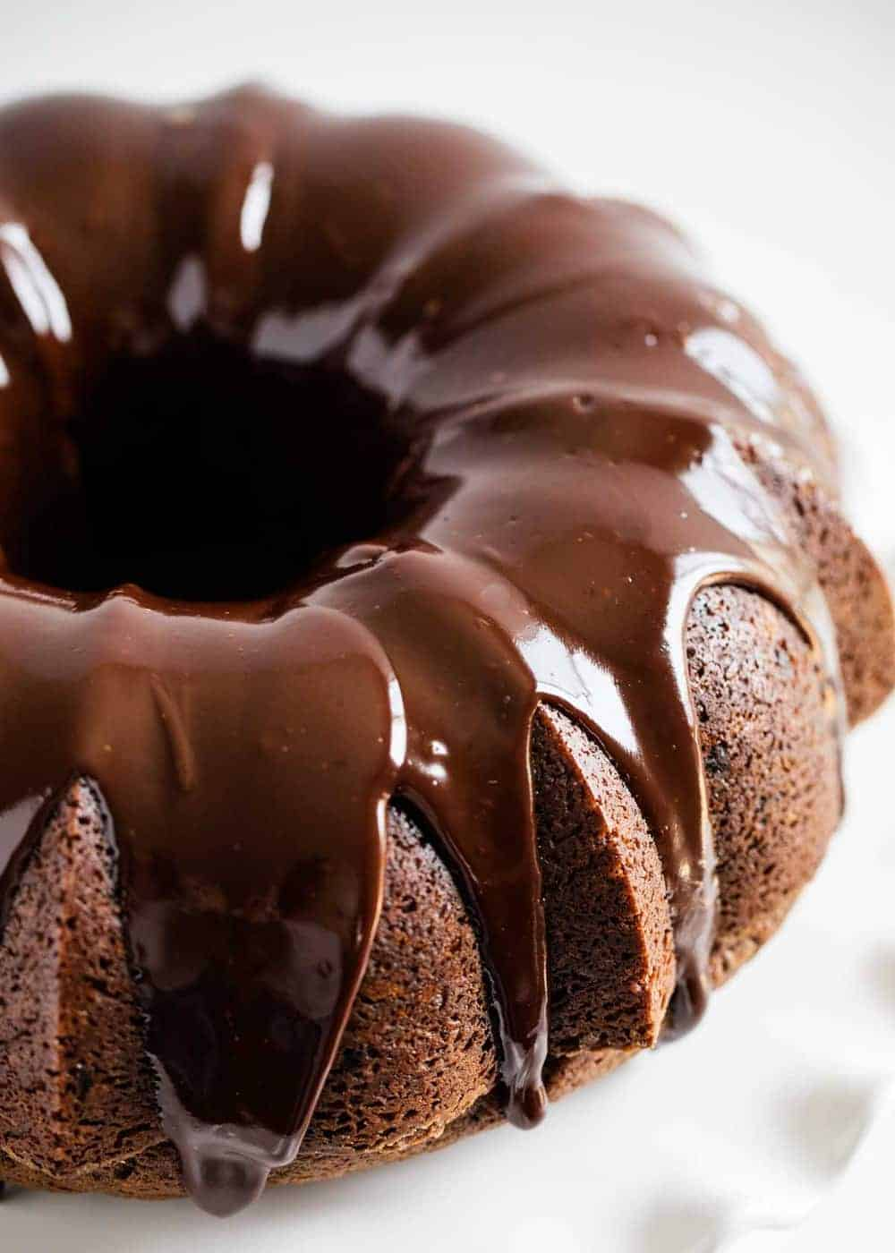 chocolate bundt cake on white cake stand