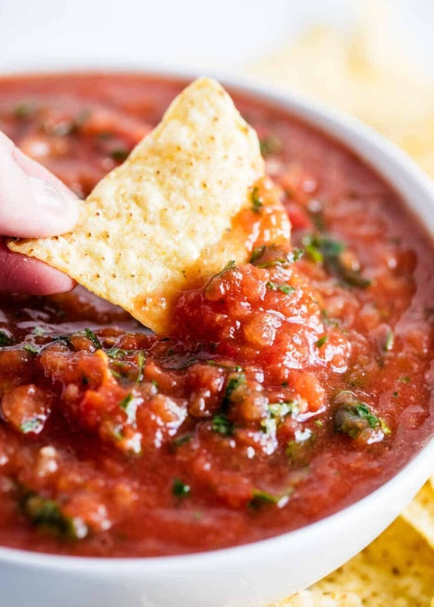 tortilla chip dipped in bowl of salsa