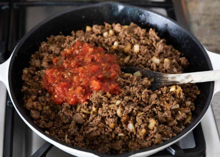 mixing salsa into a pan of taco meat