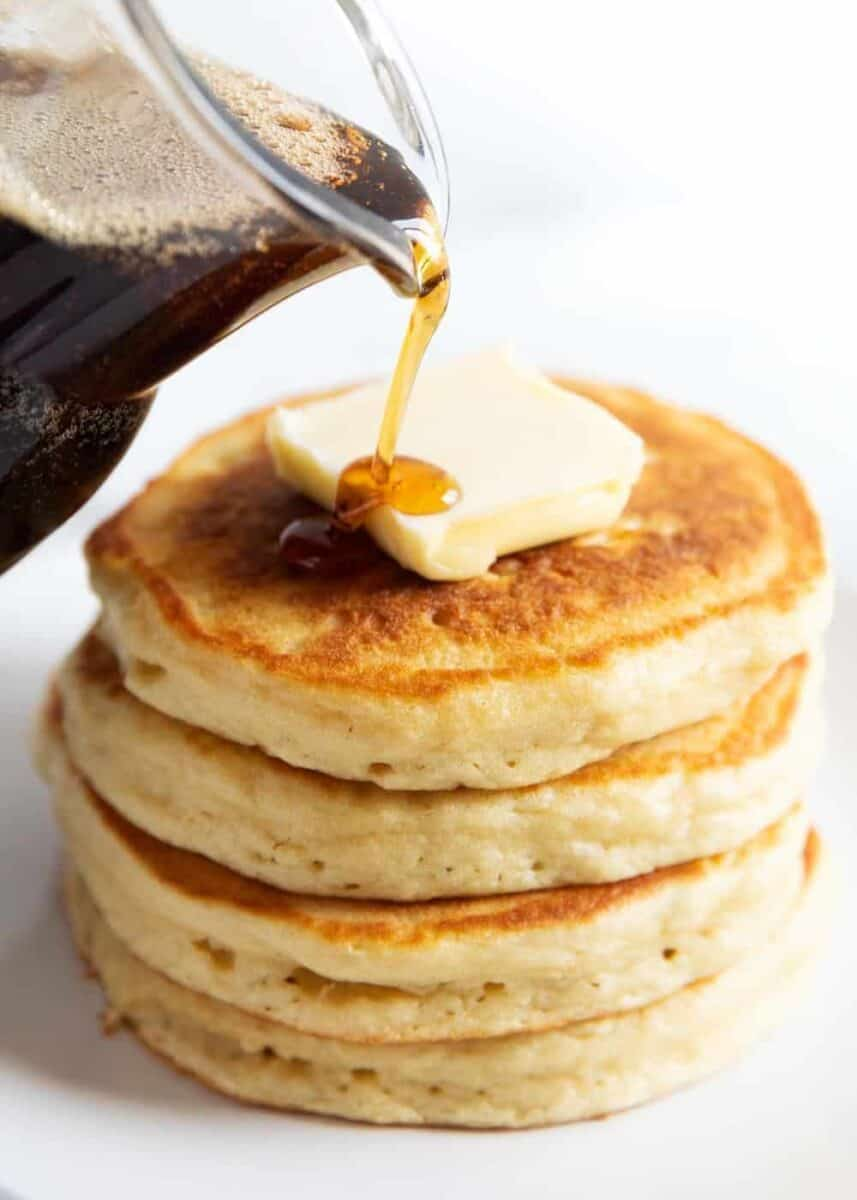 pouring syrup on a stack of buttermilk pancakes