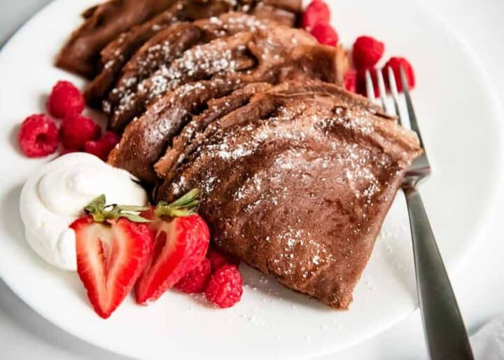 chocolate crepes on a plate with fresh berries