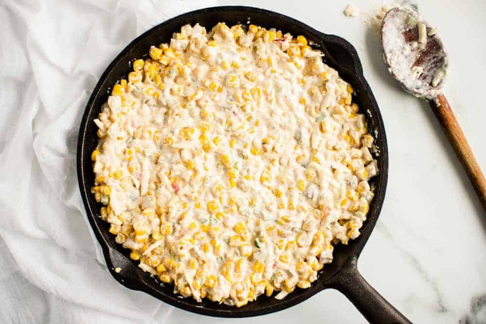 corn dip in skillet with wooden spoon on the side