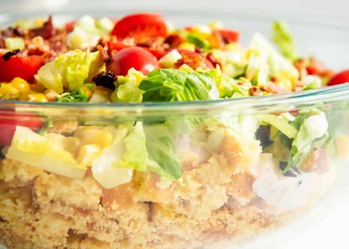 layered cornbread salad in a glass bowl