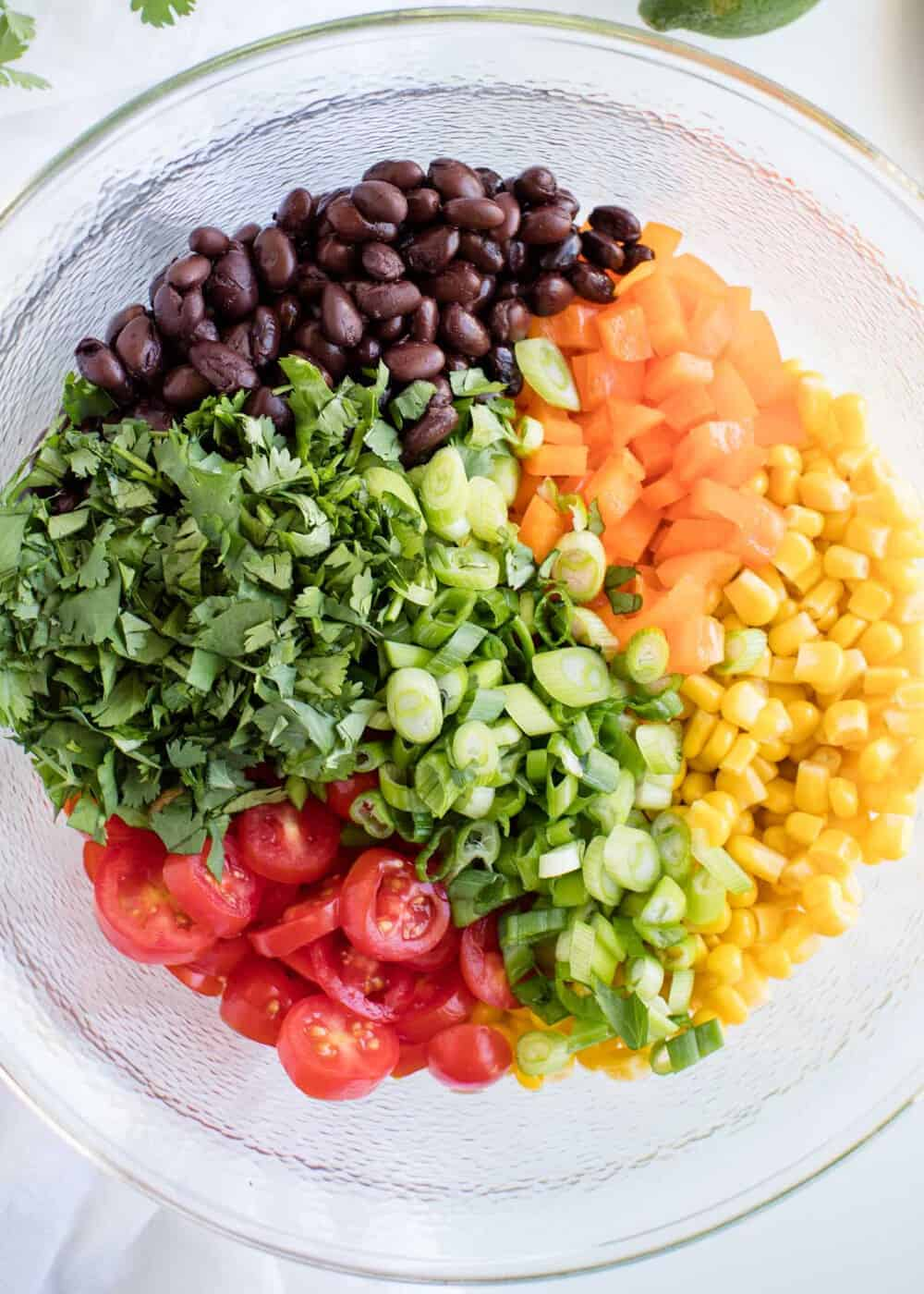 chopped ingredients for quinoa salad in a glass bowl