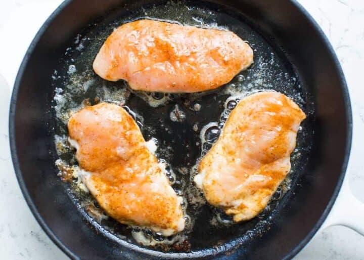 cooking seasoned chicken breasts in skillet