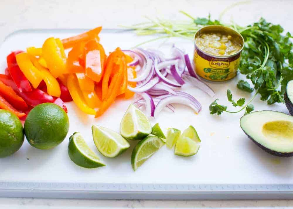 fajita salad ingredients on a white cutting board