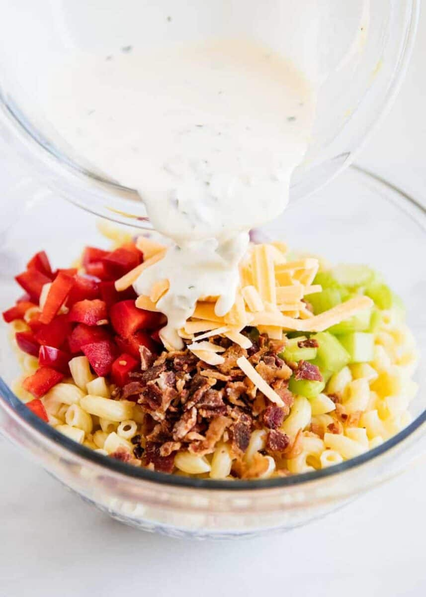 pouring dressing over macaroni salad ingredients