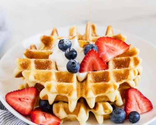 belgian waffle with berries on a white plate