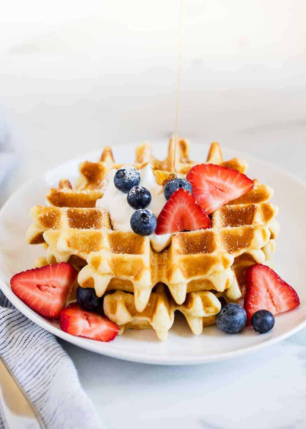 belgian waffle with berries on a white plate and syrup being poured