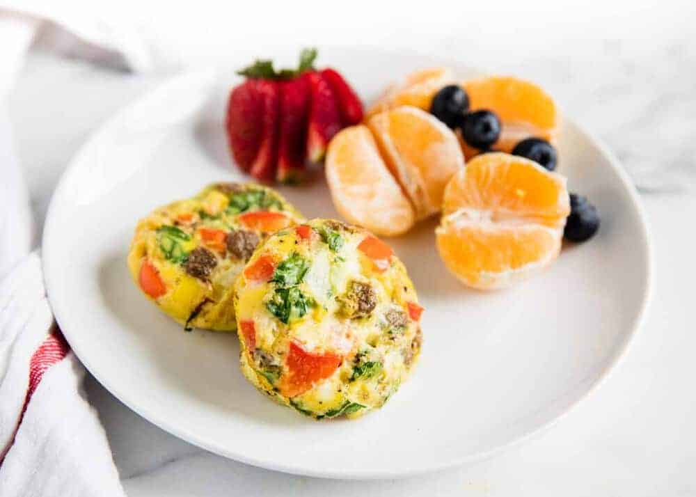 breakfast egg muffins on white plate with fruit