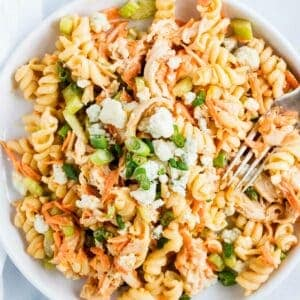 buffalo chicken pasta salad on a white plate with fork