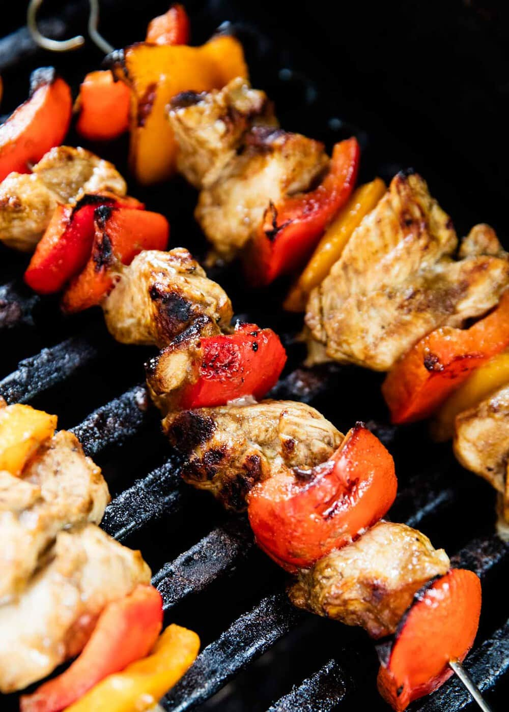 chicken kabobs being cooked on the grill