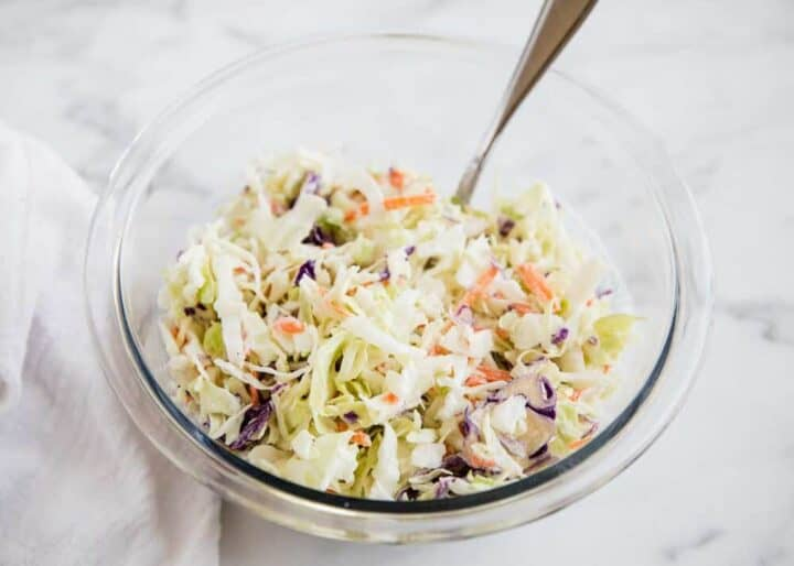 coleslaw in a glass bowl with a silver spoon