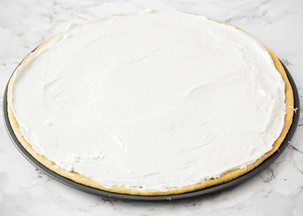 sugar cookie crust in a pizza pan with cream cheese frosting on top