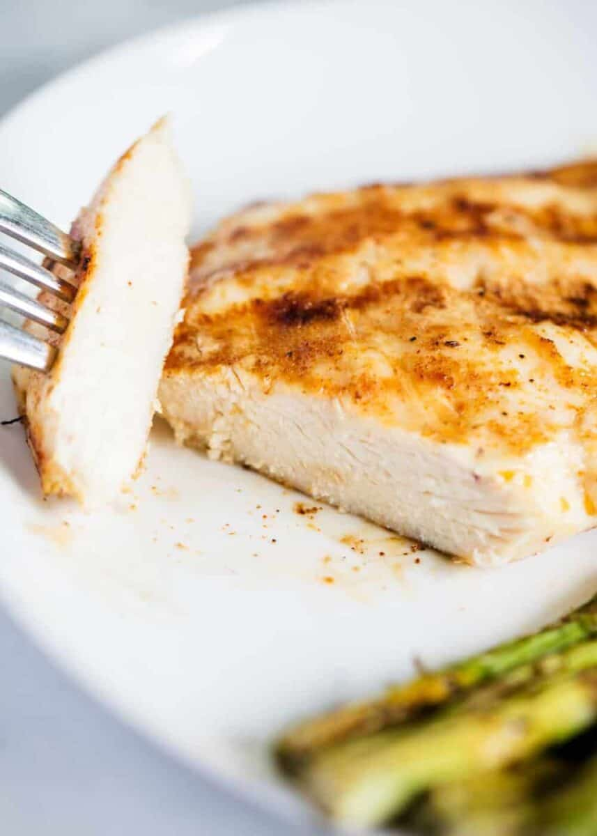sliced grilled chicken breast on white plate