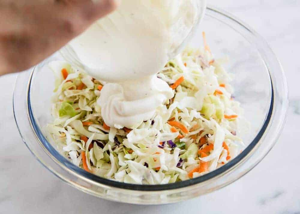 pouring dressing over coleslaw mix in a glass bowl
