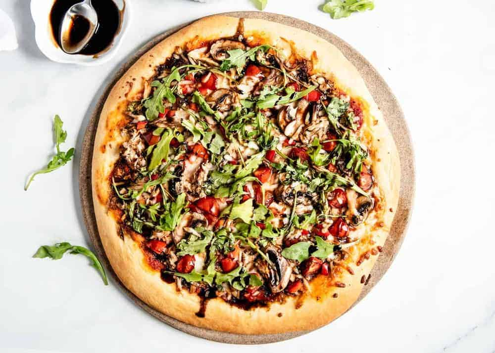 vegetable pizza on pizza stone topped with arugula and balsamic glaze