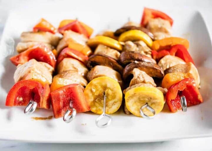 shish kabobs ready to be grilled on white plate
