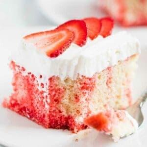 jello poke cake with whipped cream and strawberries
