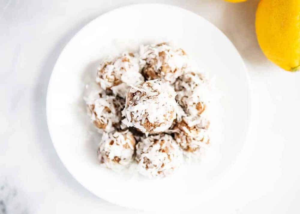 stack of lemon coconut energy balls on a white plate