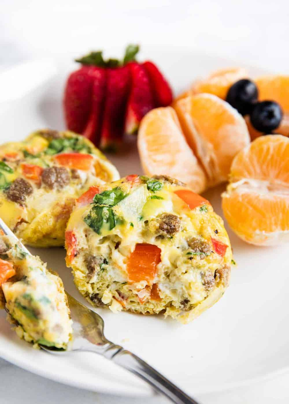 muffin tin eggs on white plate with fruit