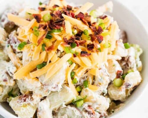 potato salad with cheese and bacon in white bowl