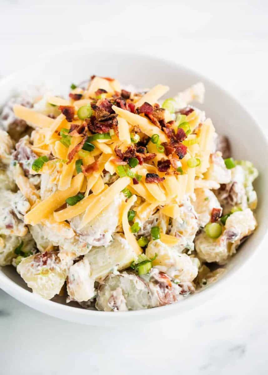 loaded potato salad with cheese and bacon in white bowl