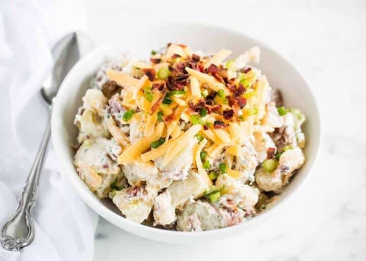 loaded potato salad in white bowl