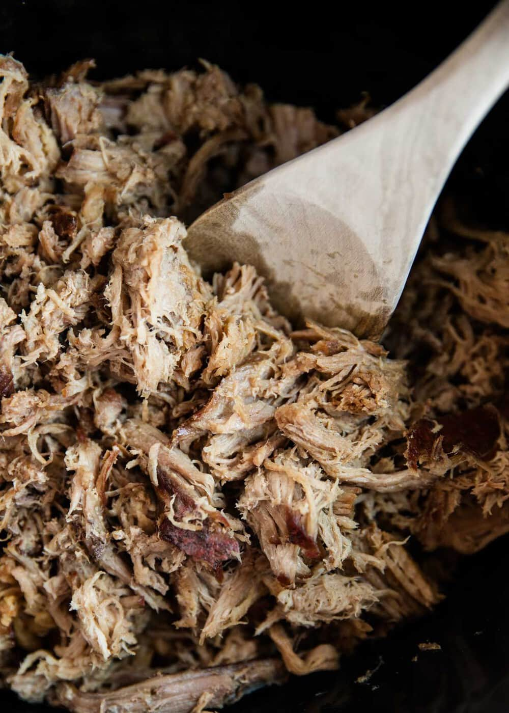 kalua pork in the slow cooker with a wooden spoon
