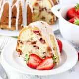 strawberry sour cream cake on white plate with strawberries