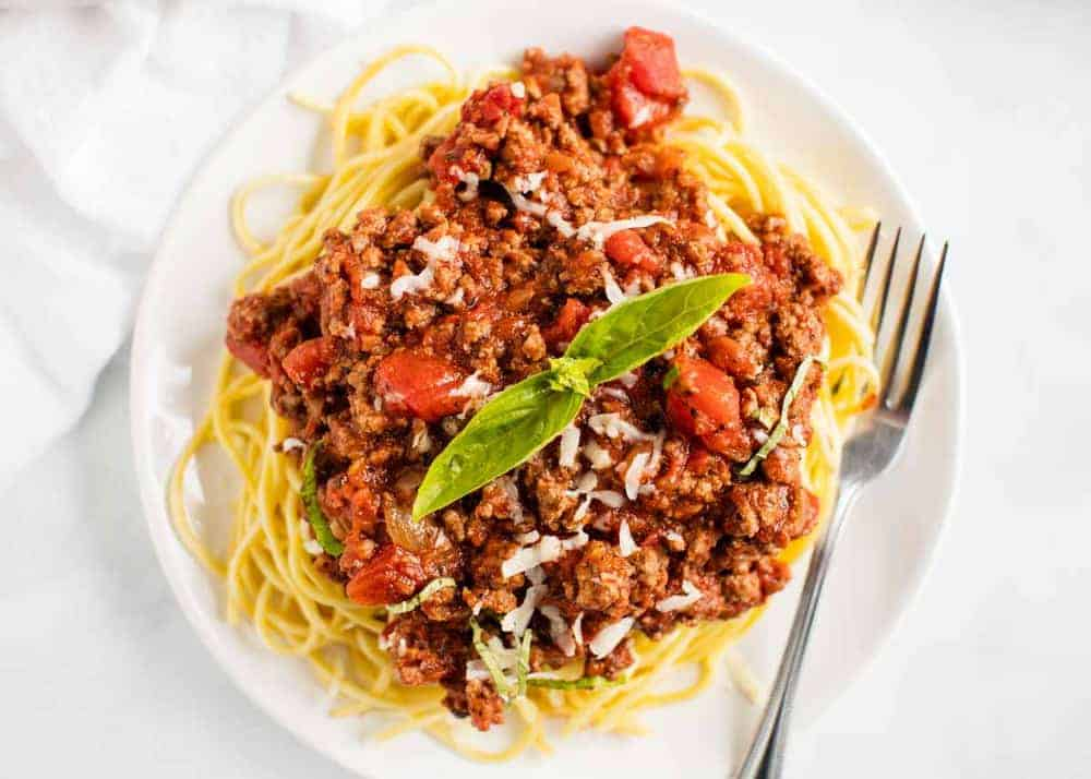 spaghetti and meat sauce with basil on a white plate