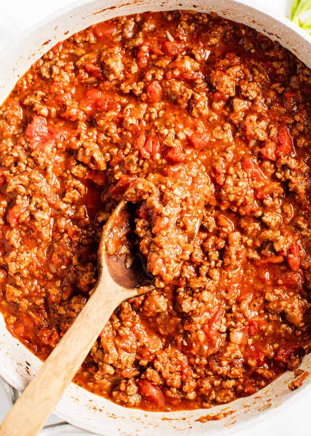 spaghetti meat sauce in a pan with a wooden spoon