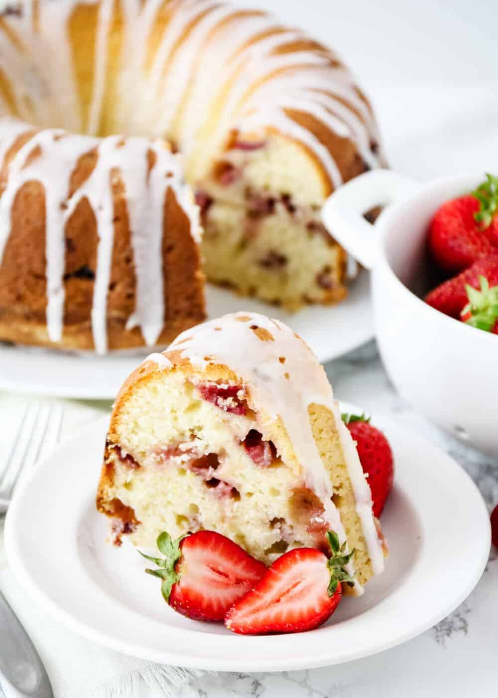 strawberry bundt cake on white plate with fresh strawberries