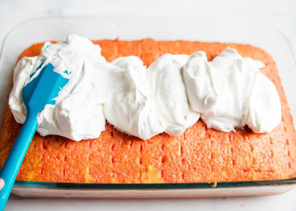 spreading whipped cream on strawberry jello cake with a spatula