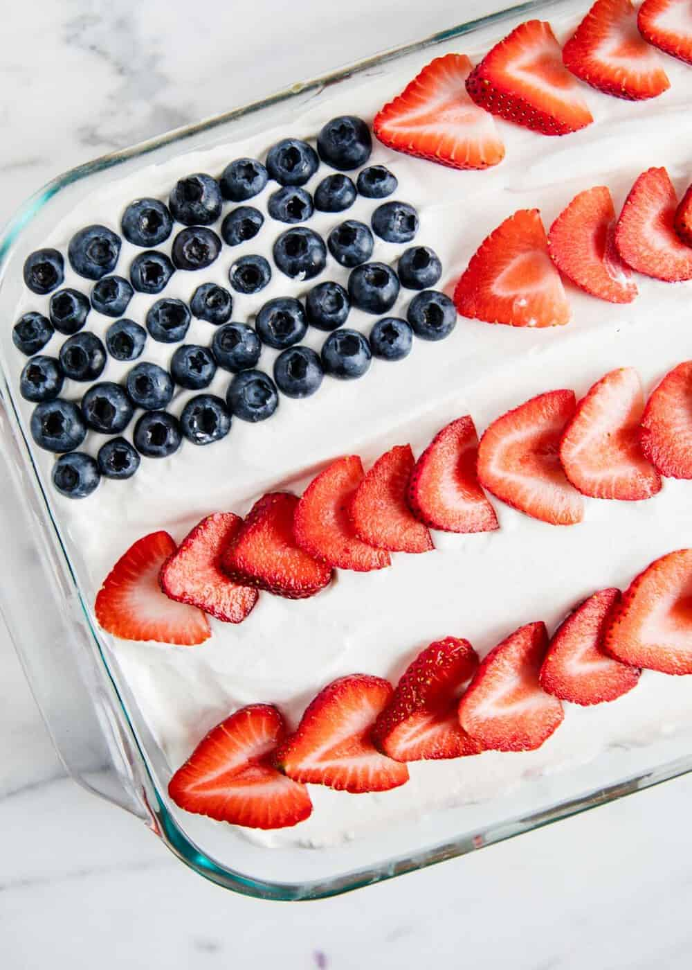 jello poke cake topped with berries in the shape of an American flag