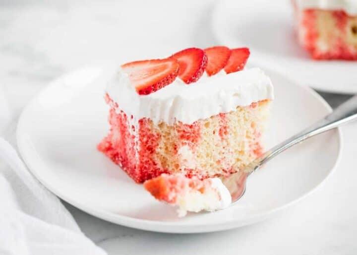 strawberry poke cake on a white plate
